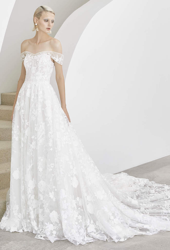 Woman posing in white, off the shoulder wedding dress next to a staircase