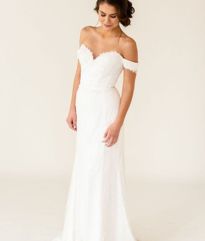 Model posing in off the shoulder white wedding dress