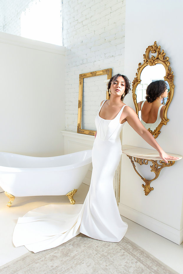Woman posing in square neck, white wedding dress in front of a gold ornate mirror and large white vintage bathrub.