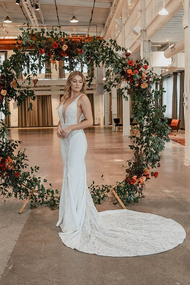 Woman standing in front of floral arch in white lace wedding dress.