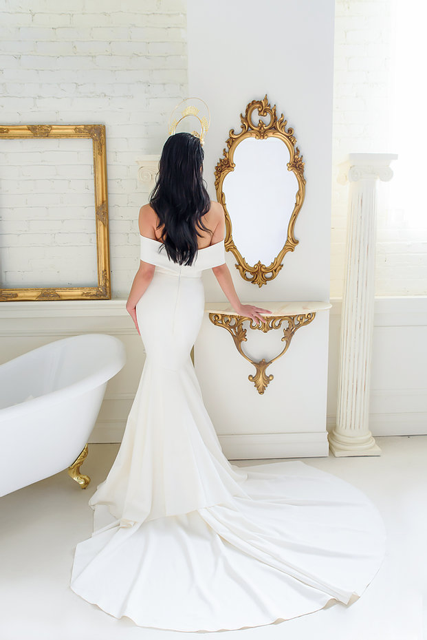 Woman in a Colby John wedding dress with her back facing the camera in a long, white, off the shoulder mermaid wedding dress. She is standing next to a white bathtub and looking towards a gold ornate mirror,