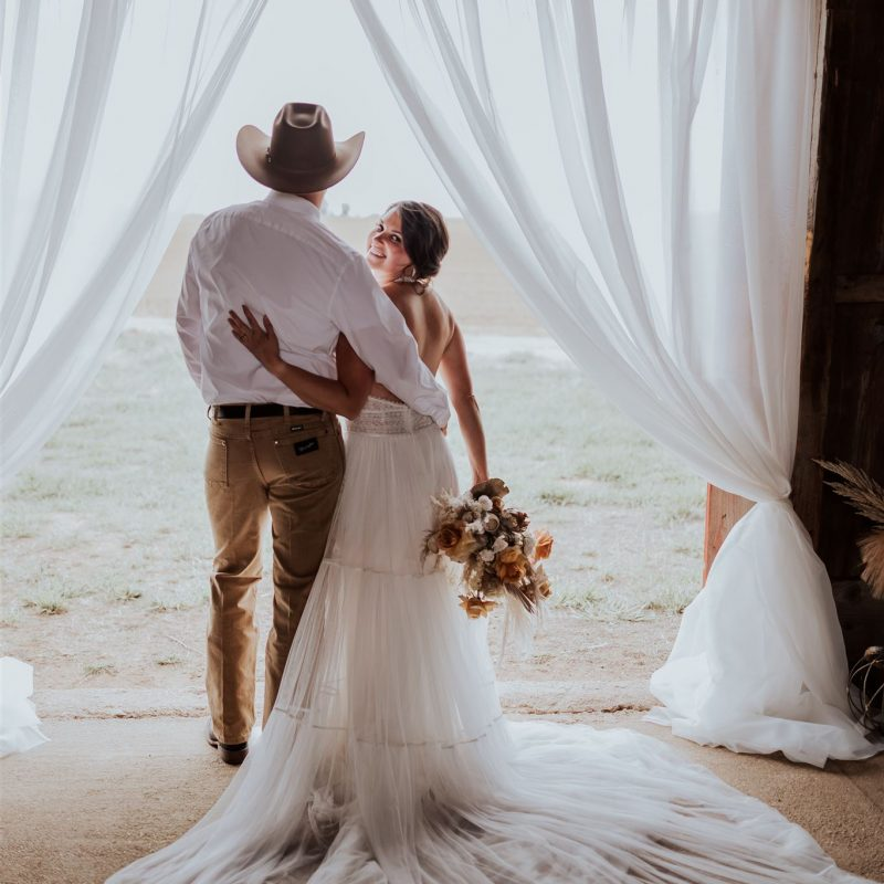 Bride and groom in doorway of the barn with backs facing the camera and the brides head is turned.