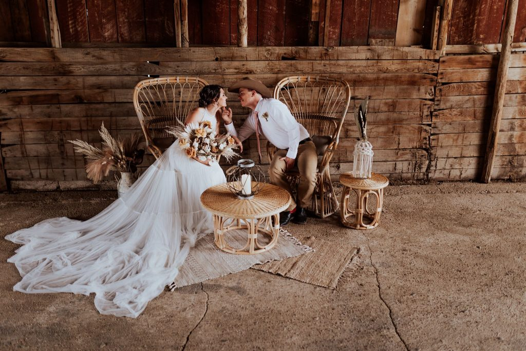 Bride and groom sitting in large wicker chairs, about to kiss