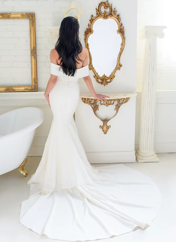 Runaway Bridal designers, Colby John. A woman standing in a white bathroom in a white wedding dress