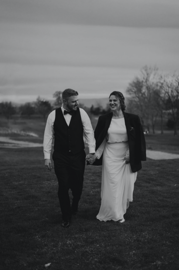 A black and white photo of bride and groom walking towards the camera. The bride is wearing the grooms jacket over her wedding dress