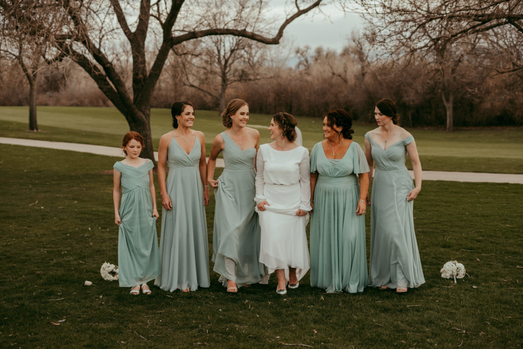 A bride holding up her dress to show her shoes. She is surrounded by her five bridesmaids in green dresses.