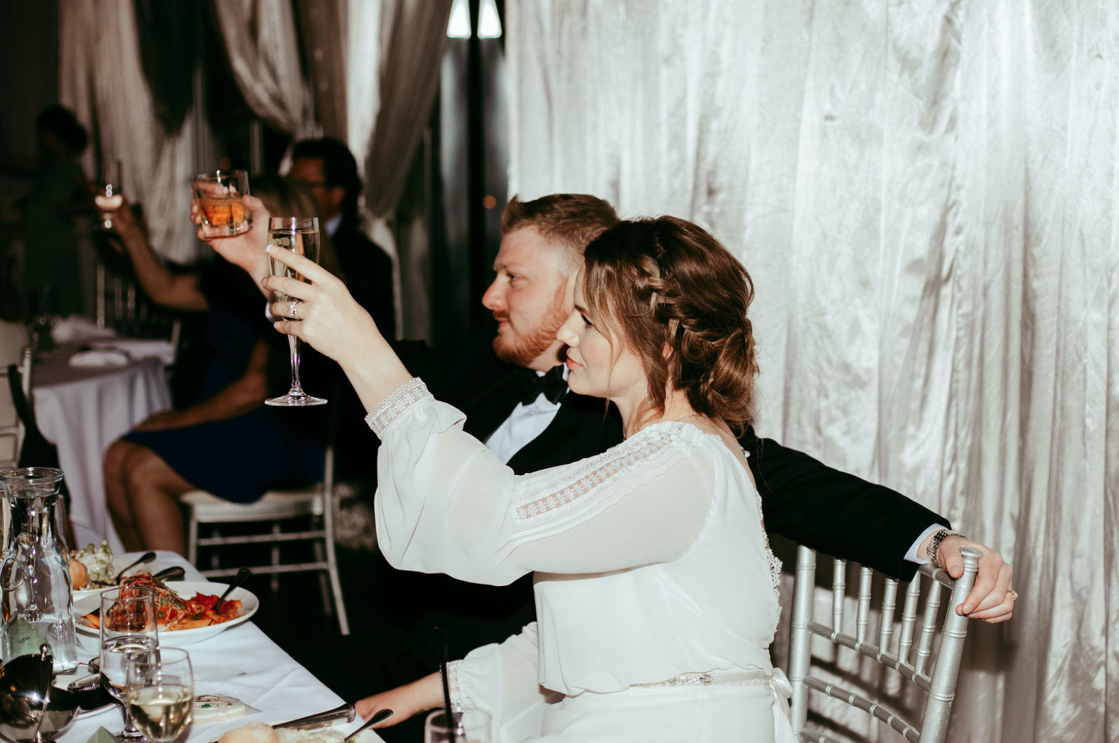 Bride and groom at the head table toasting eachother