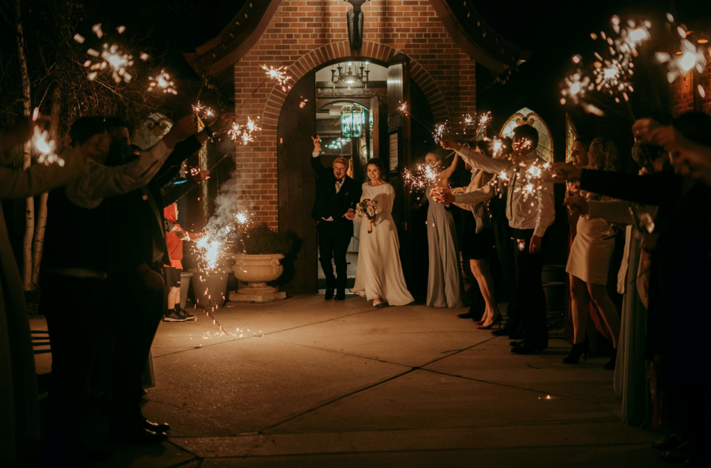 Bride and groom walking through a line of their friends and family holding sparklers