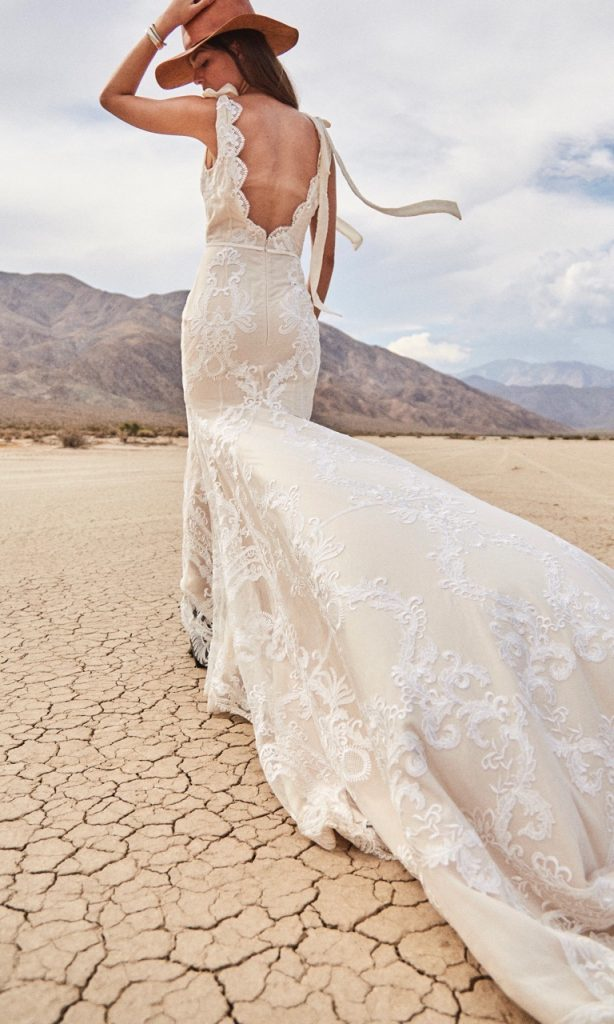 Woman walking in the desert in a flowing off white Daughters of Simone wedding dress, holding her brown hat on her head