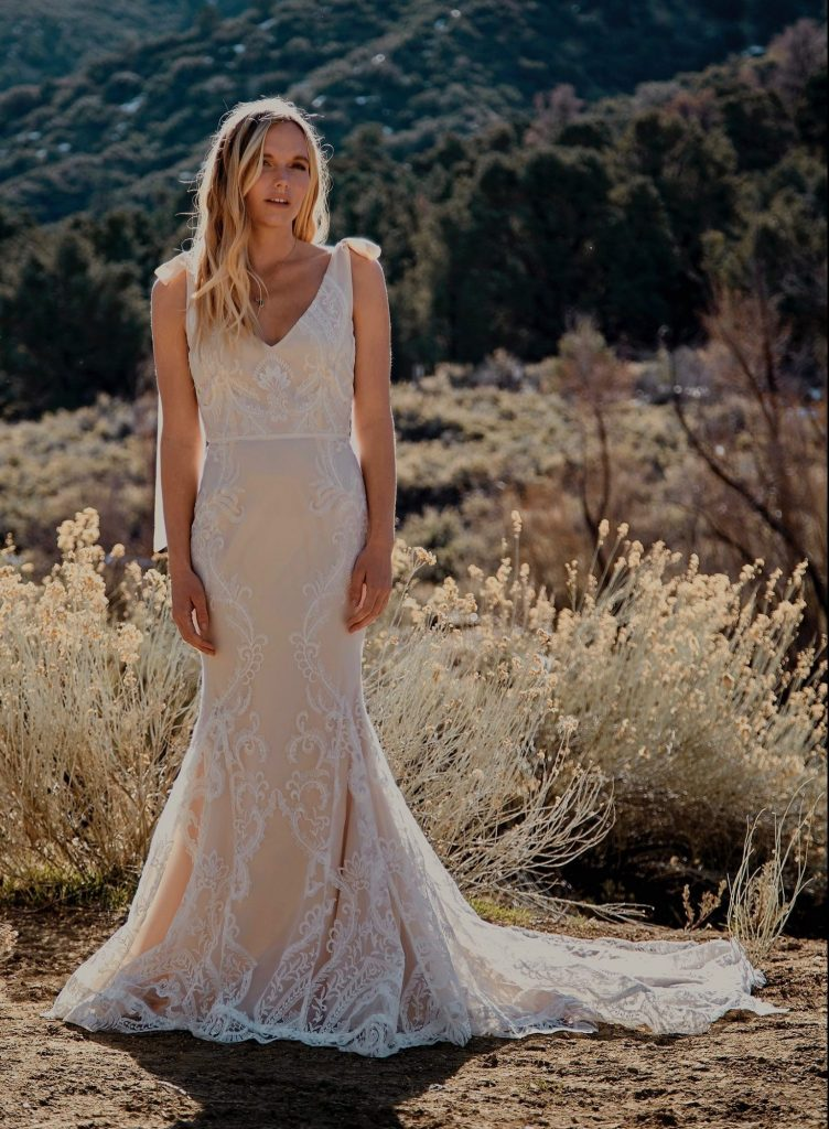 Runaway Bridal designers, Daughters of Simone. Bride standing in the desert in a long off white wedding dress.