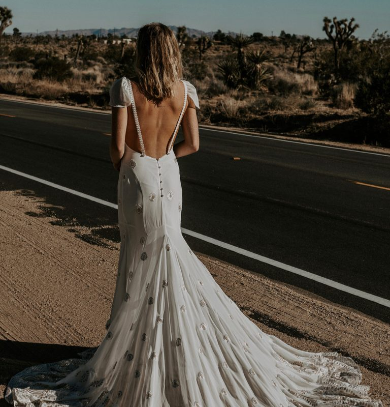 A woman in a wedding gown near the side of a dessert road