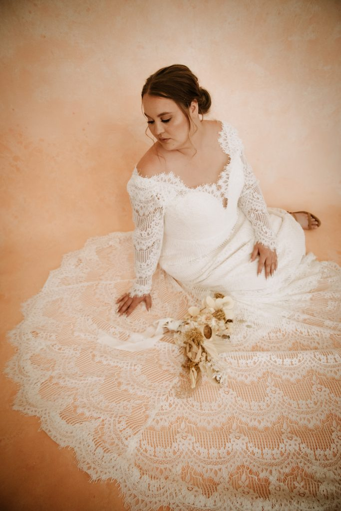 A bride sitting on the floor surround by her wedding dress train.