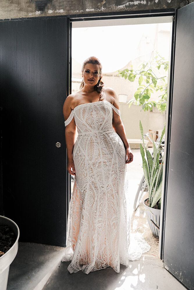 Woman in blush Studio Levana boho wedding dress. Standing in a doorway.
