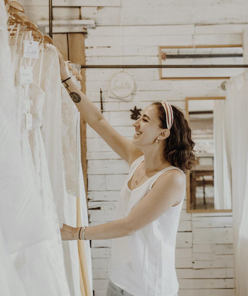 Designer, Marteal Mayer, going through wedding dresses in her studio.