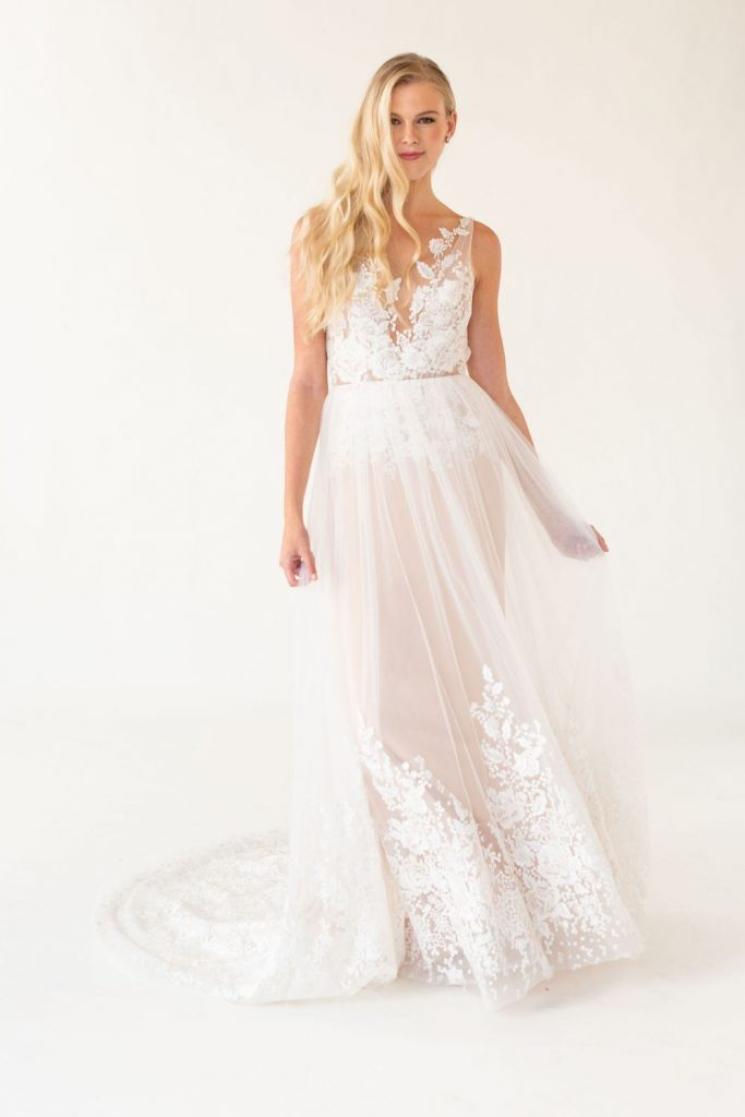 Model wearing sample sale dress. Cadence. A blush toned lace and tulle wedding dress.