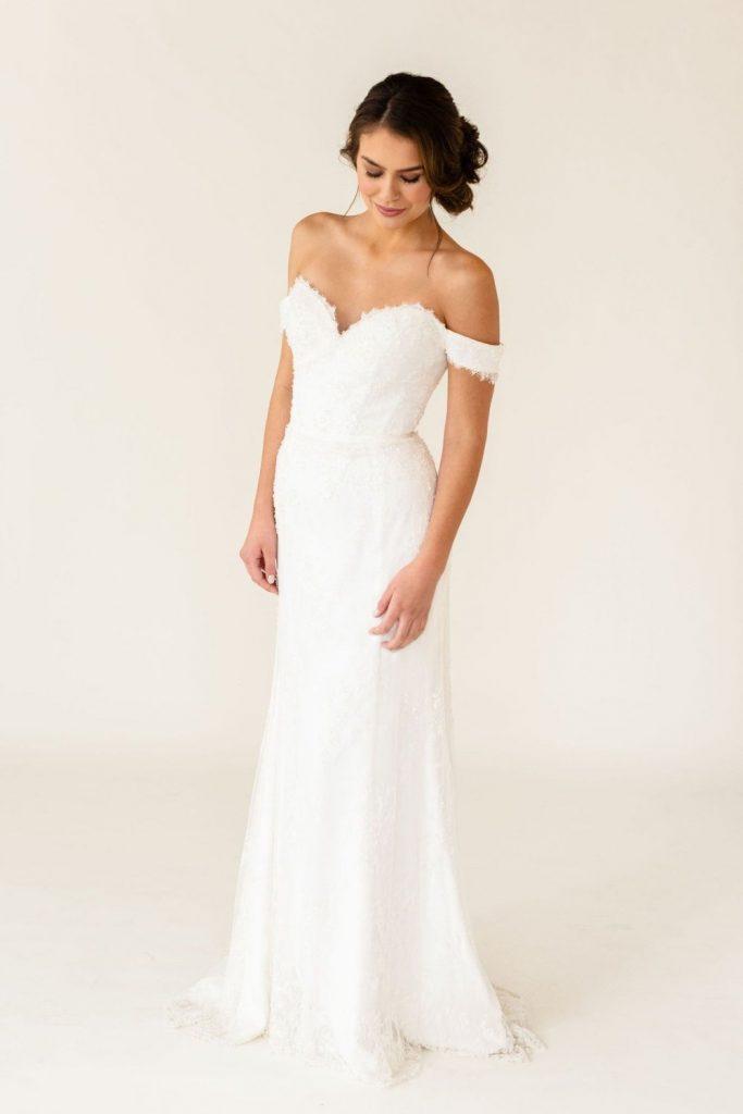 Model wearing sample sale dress, Isla. A off the shoulder, sweetheart neckline, fit and flare wedding dress.