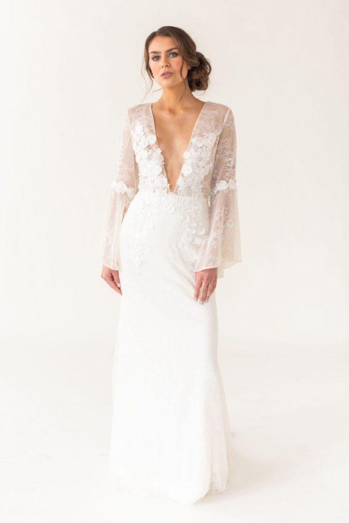 Model wearing sample sale dress, Rosalie. A plunge neck, lace boho wedding dress.