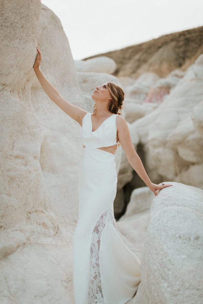 Model in sample sale dress, Skye. Models hand is raised on a rock at the Paint Mines Park.