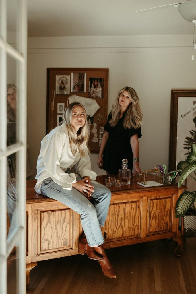 Daughters of Simone designers, Ashley and Brittany sitting in their office