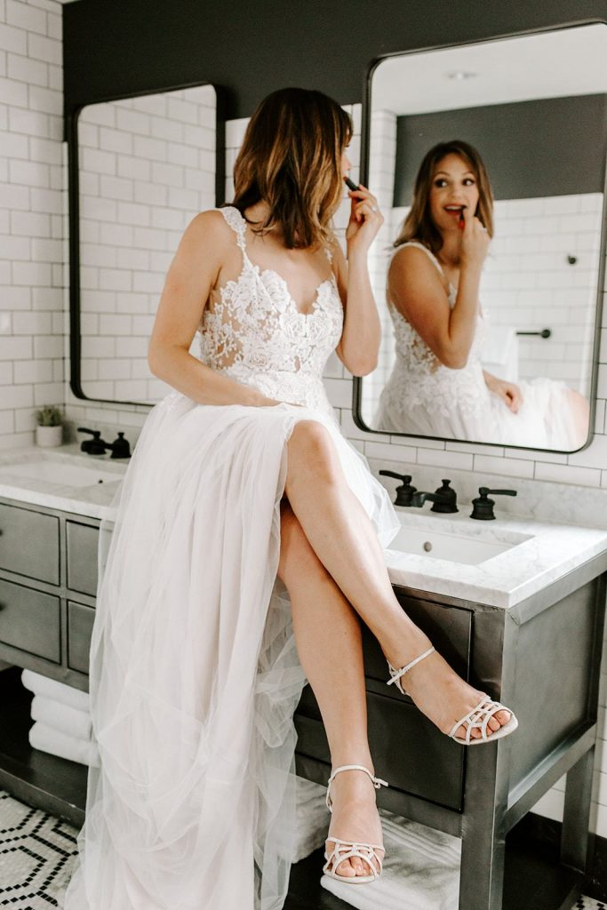 Designer Desiree Hartsock sitting on a sink in a blush toned wedding dress, putting on lipstick.