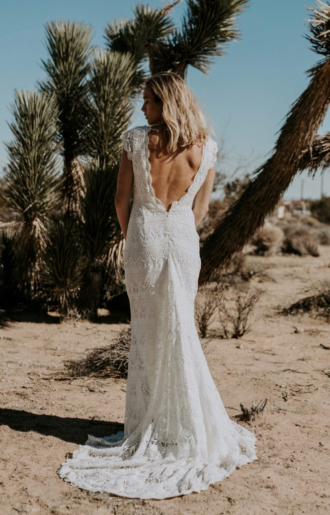 A woman standing in a desert behind palm trees, wearing a white crochet lace Daughters of Simone wedding dress.