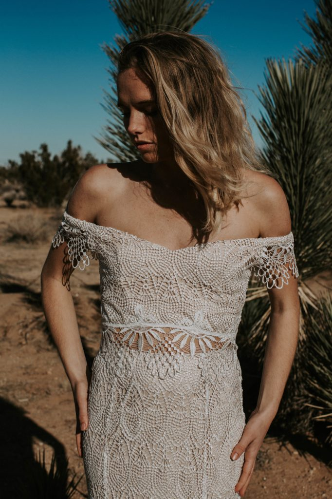 Woman in a two piece crochet lace Daughters of Simone wedding dress, standing in a desert.