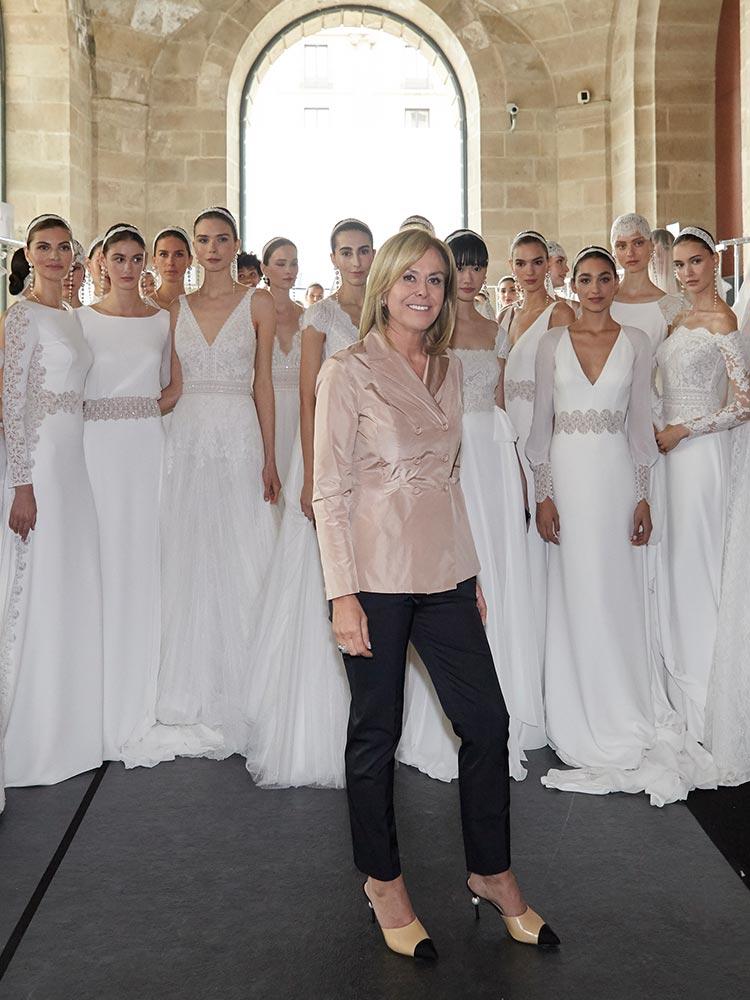 Designer, Rosa Clara, standing in front of several models in wedding dresses