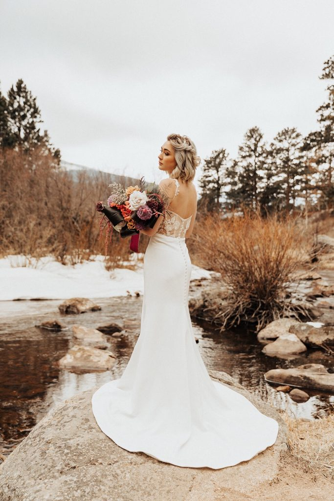 A bride standing outside holding a floral bouquet. She is wearing a Desiree Hartsock crepe wedding dress.