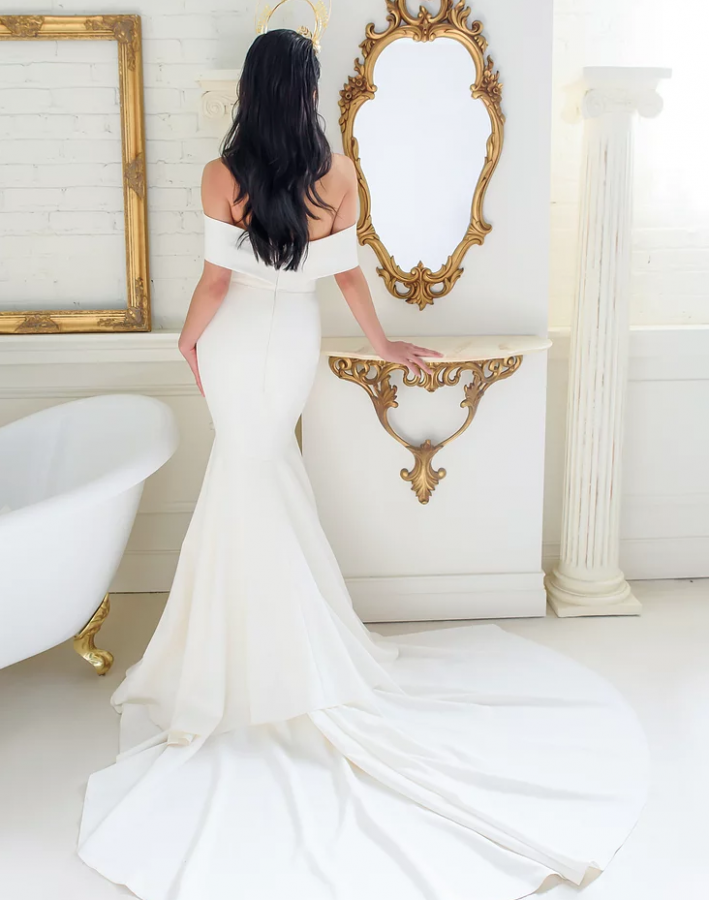 A woman standing in a white bathroom in a white wedding dress