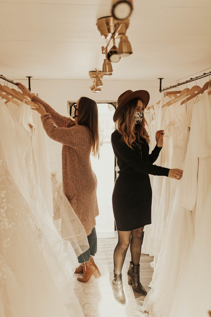 Two women in a truck looking at wedding dresses