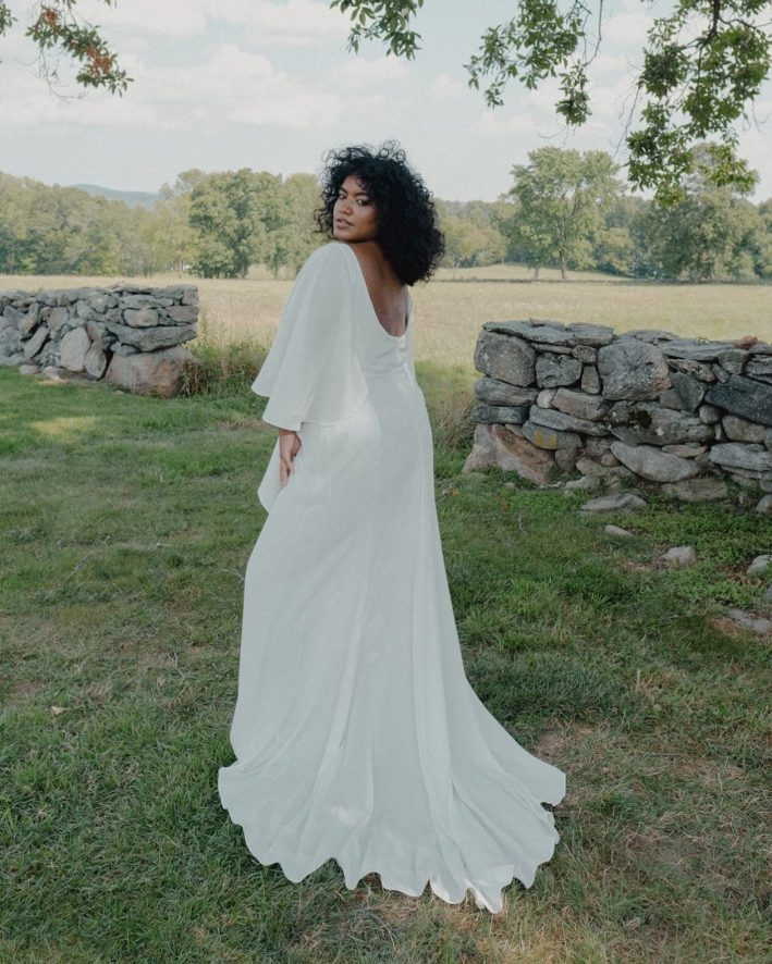 Women standing in grass in white flowing wedding dress