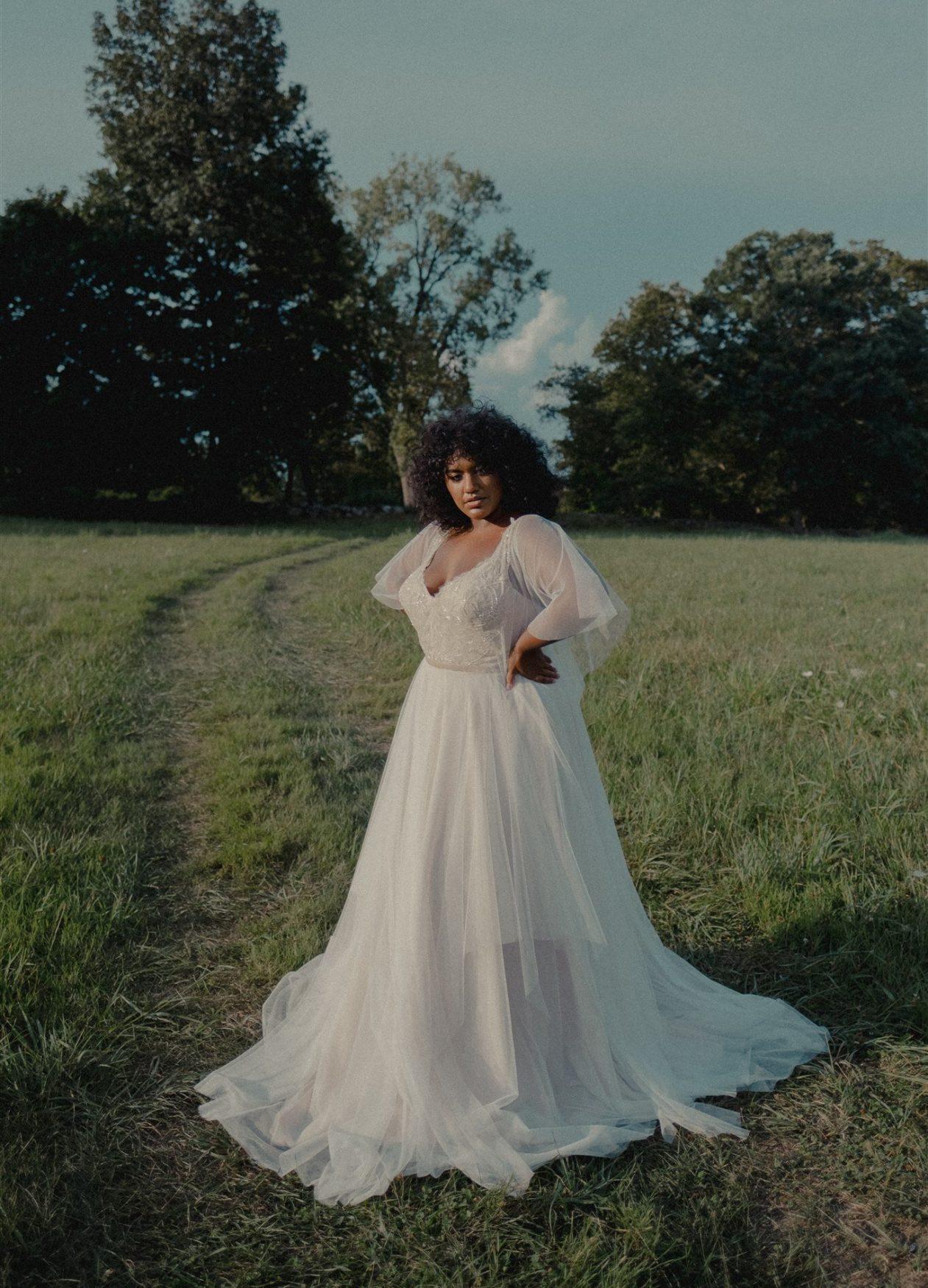 Women standing in field in white wedding dress