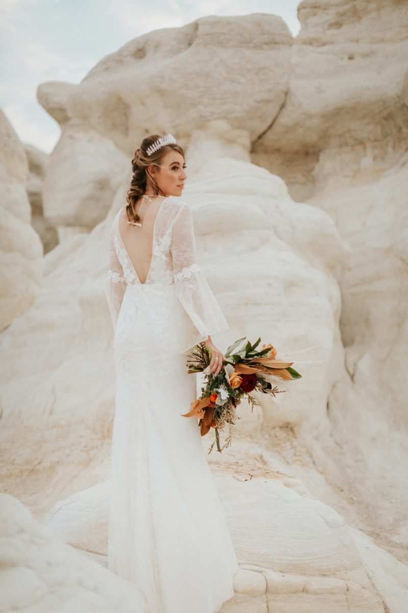Bride in long sleeve, lace wedding dress, tiara, and bouquet in hand